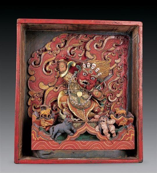 大红司命主,藏语称江姆僧或姊妹护法神。显红色威严相,系密宗马头明王眷属中的男红面狱主。主管各类鬼怪。原为拉萨色拉寺杰僧院最主要的保护神。据藏文经典记载,此护法居住于血海围绕的宫殿,宫中由人血和马血形成的湖中有一座红色的四角铜山,山顶的太阳莲花便是此尊的居处,此尊身着犀牛甲,四肢短粗,高大威猛,嘴角冒出湿热的血泡。头向左倾,面庞方正,大耳贴面,耳饰,血盆大口,龇露獠牙,头戴五骷髅冠,发呈火焰状,皱眉蹙额,三目怒视佛教之敌。左手当胸结说法印,右手挥舞鱼鳞柄宝剑举过头顶。左足踏人,右足踏马,立于莲花宝