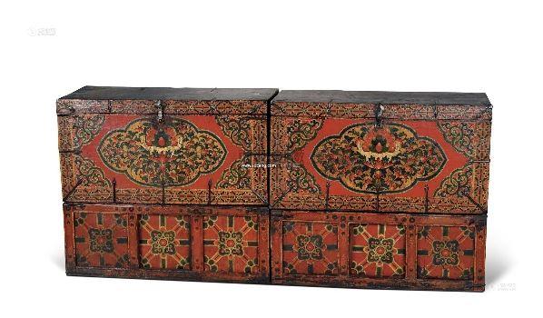 89×33×39cm;89×44×39cm西藏中部与其它木箱不同,这对木箱还带有一对别致的台座。台座前面有挡板,其余几面皆无,中间有小门,可左右推拉,门上及两侧有几何花纹彩绘。这样的台座实用而美观,放在地上即可通风干燥保护箱子,又可储存杂物。箱上正面有精美彩绘,画面四周有几何纹边框,边框纹饰与台座纹饰类似,只是形体较小。框内四角有卷草纹装饰,中央如意形画框内绘有精美的宝珠花卉图案。芳草茵茵、百花争艳,众花环绕之中有一光彩夺目的聚宝盆,盆装着宝石、珊瑚、象牙等各色珍宝