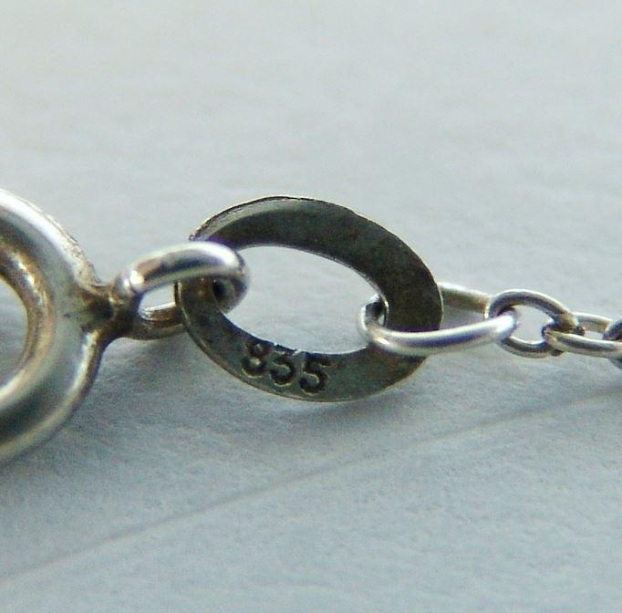 链坠镶有一颗椭圆形珊瑚珠,最大直径为:10毫米.有天然纹路.